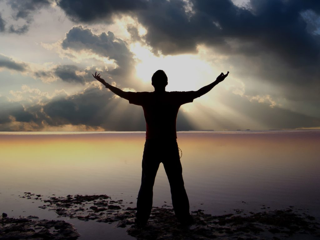 Image: Man with arms raised to sunset oover a body of water